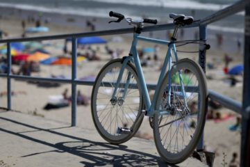 A cheap fixie bike leaning against the fence near the beach