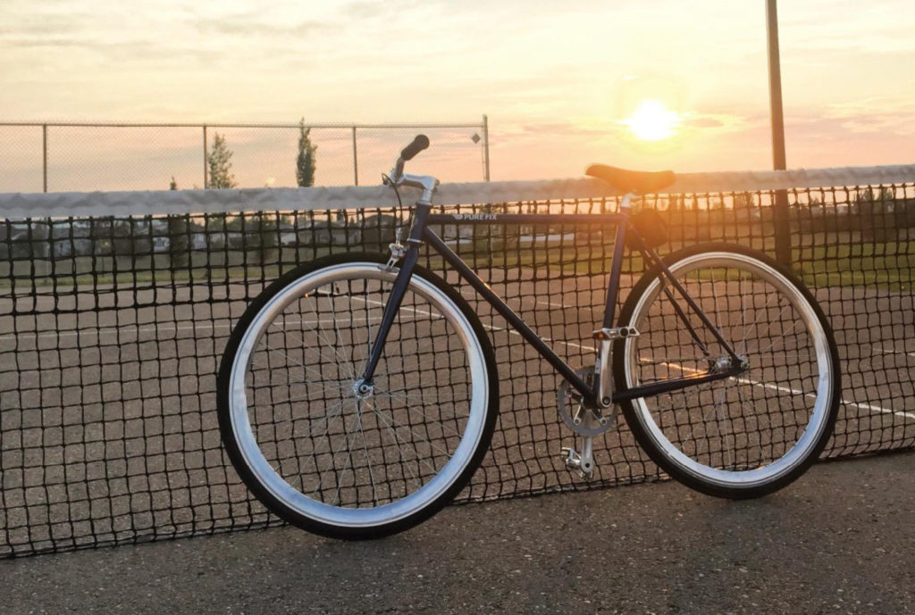 An image of the pure fix fixie bike leaning on a tennis net in the sunset