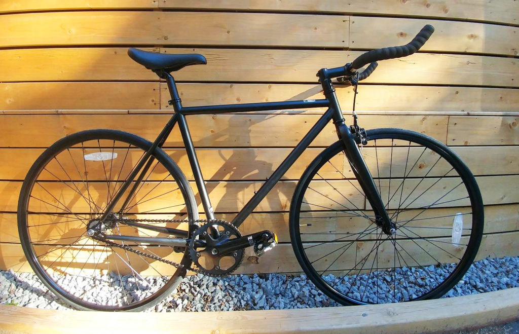 An image of the state cycle fixie bike leaning against a wall