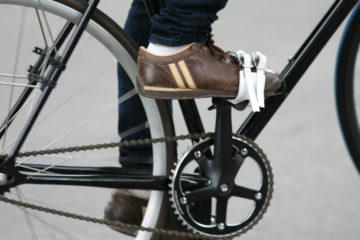 A close up of a foot on a pedal with a fixie pedal strap.