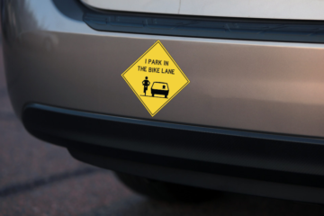 """The bumper of a car with the """"I park in the bike lane"""" sticker"""
