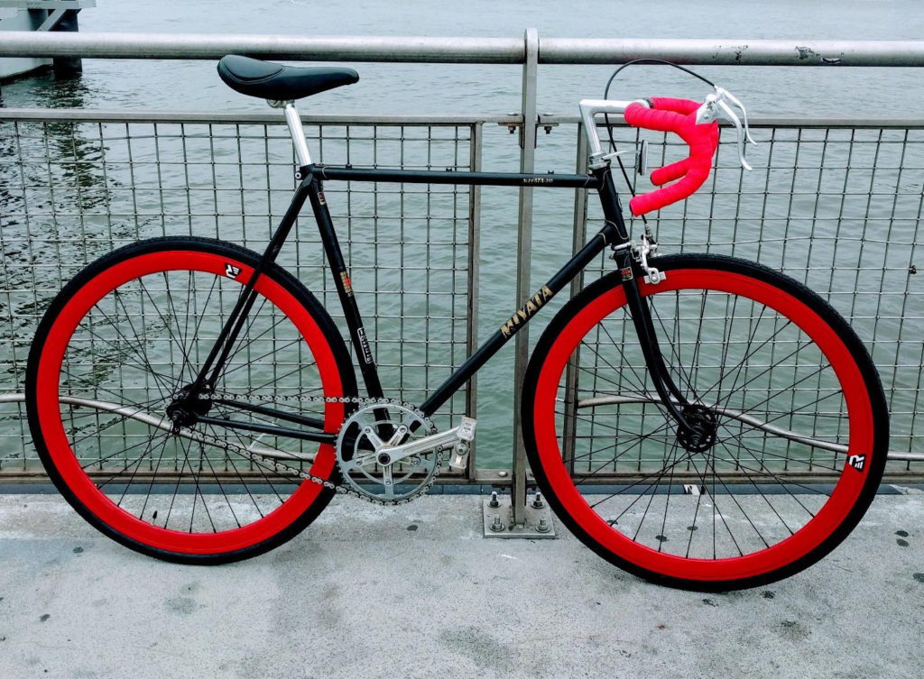 An image of the retrospec fixie wheels on a bike leaning on a fence