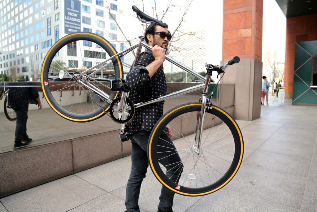 An image of a man holding up a bike intended to show off the wheels for the Retrospec Mantra Fixe Wheels Review