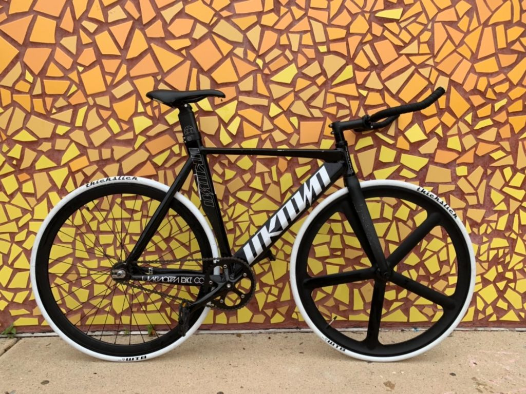An image of the solomone front fixie wheel on a bike leaning against a wall