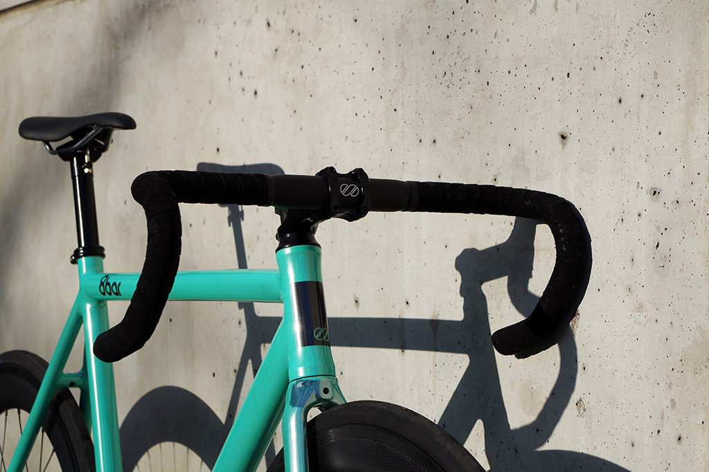 An image showing the best fixie drop handlebars on a teal bike leaning against a wall.