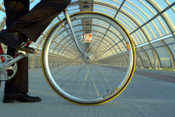 An image of a front fixie wheel lined up with an overground walkway