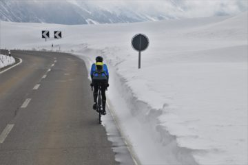 An image of a bike rider cycling away from the camera along a highway in the winter.