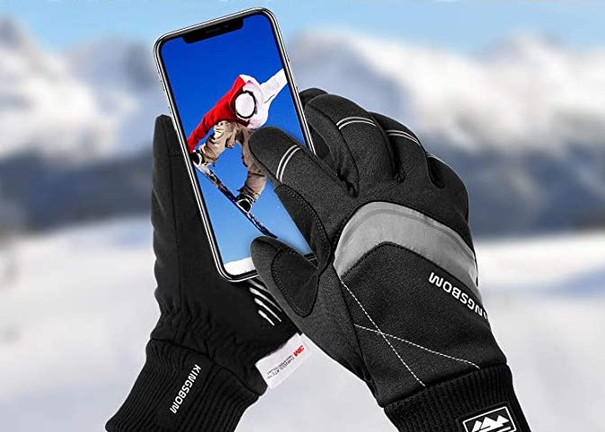 An image of winter gloves touch a phone screen, meant to show the importance of having proper riding gloves for winter bike riding.