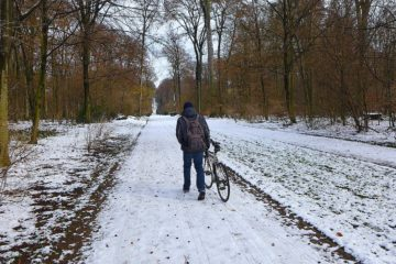 An image of a cyclist walking his bike in the snow, intended to show the importance of fixie winter tires for a review of the best fixie winter tires