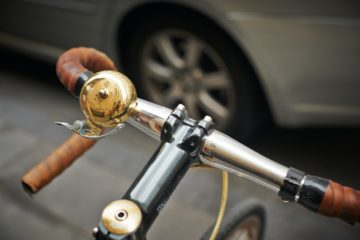 An image of fixie handlebars with a car in the background, serving to show off a range of the best fixie handlebars for a list review.